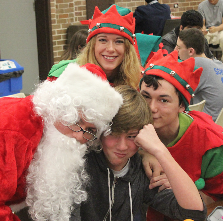 Santa and his two elves get close and personal with sophomore Jimmy Robinson.