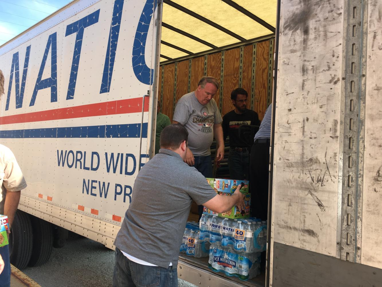 Employees help load the trailer full of donated supplies.